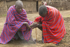 Masai male making fire by rubbing sticks together in village near Tsavo National Park, Kenya, Africa Royalty Free Stock Photography