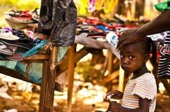 Masai Mara, Kenya 18 DE DEZEMBRO DE 2011: Menina do Kenyan em um mercado com sua mãe em Mombassa Imagem de Stock Royalty Free