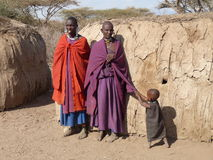 Masai parents with child tugging at mother's clothes for attention. Unidentified Masai family in traditional blankets and jewelry with mud huts in background Royalty Free Stock Image