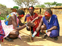Masai people making fire. At the masai village in Kenya: they are trying to make fire with wood and straw in the most ancient way Royalty Free Stock Photos