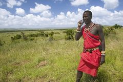 Masai in red toga talks on his cell phone from the grasslands of the Lewa Wildlife Conservancy in North Kenya, Africa Stock Photos