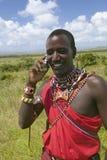 Masai in rode toga spreekt op zijn celtelefoon van de weiden van de Lewa-het Wildmilieubescherming in Noord-Kenia, Afrika stock afbeeldingen