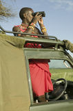 Masai scout with binoculars looks for animals from a Landcruiser during a tourist game drive at the Lewa Wildlife Conservancy in N Stock Images