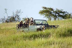Masai scout and tourists look for animals from a Landcruiser during a game drive at the Lewa Wildlife Conservancy in North Kenya,  Royalty Free Stock Photo