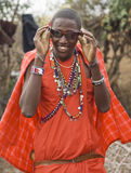 Masai with sun glasses. KENYA-2008,JULY 13. : Young Masai man trying to make a deal -sun glasses for lions tooth, native Masai village nearby Ololaimutiek Gate Royalty Free Stock Image