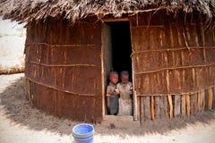 Masai Toddlers. Two Masai toddlers at the doorstep of a newly made house in their Boma. Taken at, Oldukai, Tanzania, Afriaca Royalty Free Stock Photos