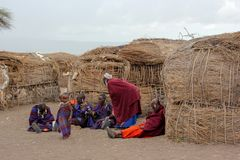 Masai villagers talking outside their straw huts royalty free stock photography