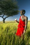 Masai Warrior near Acacia Tree listening to music on iPod by Apple in red surveying landscape of Lewa Conservancy, Kenya Africa Stock Photos