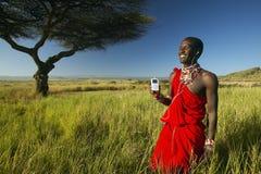 Masai wojownik blisko Akacjowego Drzewnego słuchania muzyka na ipod Apple w czerwonym przegląda krajobrazie Lewa Conservancy, Ken Zdjęcia Stock