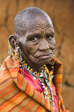 Masai Woman. KENYA-2008,JULY 13. : Old Masai woman offering for selling decorative beads and earrings in native Masai village nearby Ololaimutiek Gate to NR Royalty Free Stock Photos