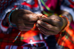 Masai woman beading. Close up of Masai woman hands threading beads Stock Photos