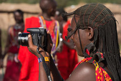 Masai woman in traditional dress using camera Royalty Free Stock Images