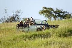 Masais kundschaften und Touristen suchen nach Tieren von einem Landcruiser während eines Spiel-Antriebs an der Erhaltung Lewa-wil lizenzfreies stockfoto