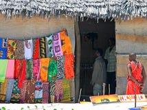 Masaistrijder die zich buiten een met stro bedekte curiosumkeet bevinden in Kenia Royalty-vrije Stock Afbeeldingen