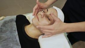 Masaje de cara Cuidado de la piel y del cuerpo del balneario Primer de la mujer joven que consigue el tratamiento del masaje del  almacen de video