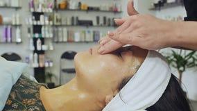Masaje de cara Cuidado de la piel y del cuerpo del balneario Primer de la mujer joven que consigue el tratamiento del masaje del  almacen de metraje de vídeo