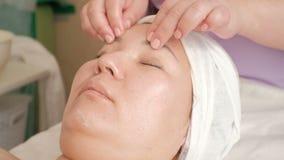 Masaje de cara del primer de una muchacha asiática en un salón de belleza Las manos de un cosmetologist realizar el procedimiento almacen de metraje de vídeo