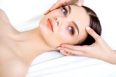 Masaje de cara. Primer de una mujer joven que consigue el tratamiento del balneario. Fotografía de archivo libre de regalías