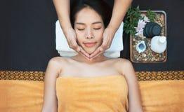 Masaje de cara Primer de la mujer joven que consigue el tratamiento del masaje del balneario en el salón del balneario de la bell foto de archivo libre de regalías
