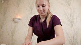 Masaje de la cintura y de la parte posterior masculinas Una muchacha que hace un masaje relajante profesional a un hombre en el s almacen de video