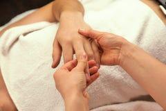 Masaje de la mano con la toalla blanca Imágenes de archivo libres de regalías