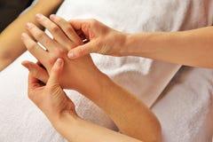 Masaje de la mano con la toalla blanca Imagen de archivo