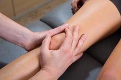 Masaje de la terapia de la rodilla de Maitland en la pierna de la mujer Imagenes de archivo