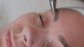 Masaje de Microcurrent alrededor de los ojos Cosmetología del hardware Las manos de un cosmetólogo profesional en guantes con almacen de video