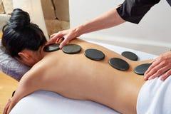Masaje de piedra caliente en fisioterapeuta de la parte posterior de la mujer Imagenes de archivo