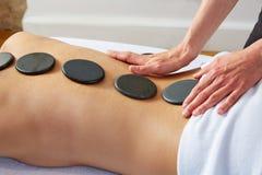 Masaje de piedra caliente en fisioterapeuta de la parte posterior de la mujer Foto de archivo libre de regalías