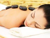 Masaje de piedra para la mujer en el salón del balneario. Fotos de archivo