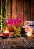 Masaje del balneario de la composición - bambú - orquídea, toallas, velas y piedras negras Imagen de archivo libre de regalías