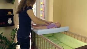 Masaje del bebé La mamá hace el vientre del niño Mentira del niño en tablero de la envoltura almacen de metraje de vídeo