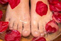 Masaje del pie con los pétalos color de rosa imagen de archivo
