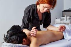 Masaje en parte posterior de la mujer con el fisioterapeuta Imagen de archivo libre de regalías