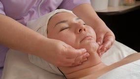 Masaje facial antienvejecedor Las manos de un cosmetologist profesional liso la piel en la cara de una muchacha asiática Spa metrajes