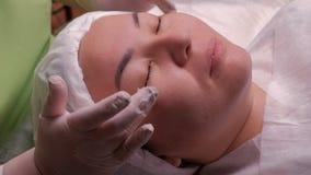 Masaje facial de una muchacha asiática en un salón de belleza Primer de las manos del cosmetólogo en los guantes blancos durante  metrajes