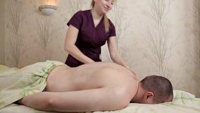 Masaje posterior Masajes del masajista el m?s de espalda del atleta de sexo masculino El masajista de la muchacha en un traje p?r almacen de metraje de vídeo