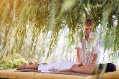 Masaje trasero de recepción femenino sonriente de un professiona del masaje imágenes de archivo libres de regalías