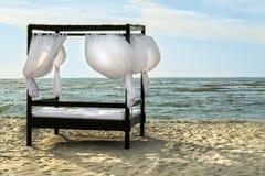 Masaje y camas del BALNEARIO con los linos y las cortinas blancos en la orilla de mar Imagen de archivo libre de regalías