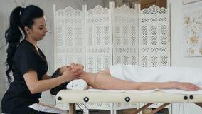 Masajista de sexo femenino enfocado que hace el masaje para el cliente joven almacen de video