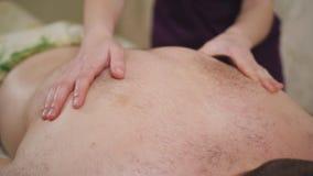 Masajista de sexo femenino que hace al hombre del masaje en el sal?n del balneario almacen de metraje de vídeo