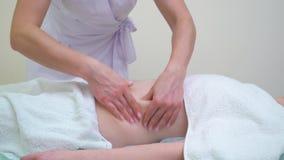 Masajista de sexo femenino que hace masaje anti de las celulitis en el abdomen de la mujer joven almacen de metraje de vídeo