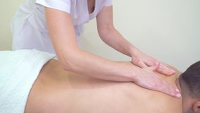 Masajista de sexo femenino usando el aceite del aroma para la parte posterior masculina moisturing para el masaje de relajación almacen de metraje de vídeo
