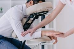 masajista que hace el masaje del brazo para el hombre de negocios fotos de archivo