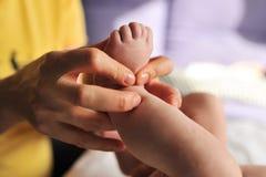 Masajista que hace el masaje para el pequeño bebé del pie fotos de archivo