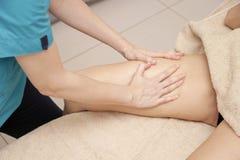 Masajista que hace el masaje terapéutico del pie para una mujer fotos de archivo libres de regalías