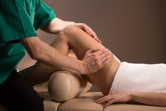 Masajista que hace masaje de la pierna Fotografía de archivo