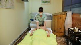 Masajista que hace masaje en mujer en el salón del balneario almacen de video