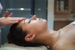 Masajista que hace masaje facial de una mujer adulta Fotos de archivo